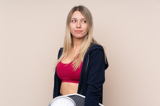 Женщина спорта молодая белокурая над изолированной стеной с веся машиной