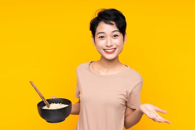 箸で麺のボウルを押しながらショックを受けた表情で孤立した黄色の壁の上の若いアジア女性