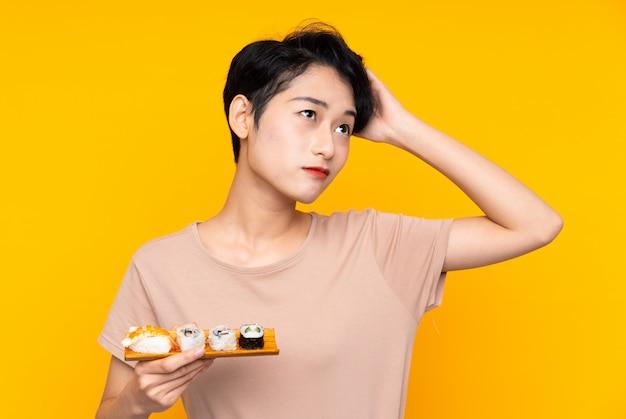 疑いを持つ寿司と混乱の表情を持つ若いアジア女性