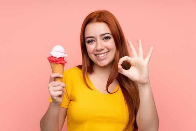Молодая женщина с корнет мороженым на изолированной стене, показывая знак ок с пальцами