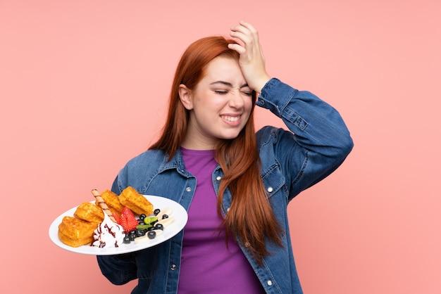 Рыжая девушка-подросток, держащая вафли над изолированной розовой стеной, что-то поняла и намеревается найти решение