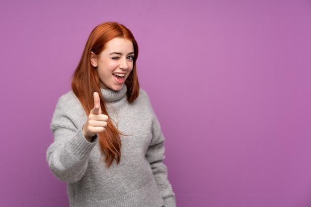 孤立した紫色の壁を越えて赤毛のティーンエイジャーの女性はあなたに指を指す