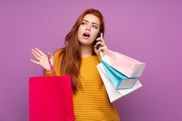 買い物袋を保持していると彼女の携帯電話で友人を呼び出す分離された紫色の壁の上の赤毛のティーンエイジャーの女性