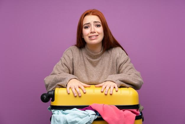 服の完全なスーツケースを持つ旅行者女性
