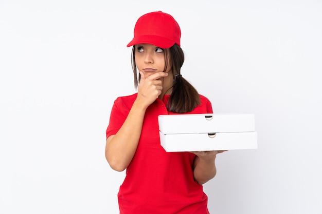 孤立した白い壁に疑問を持つと混乱の表情と若いピザ配達の女性