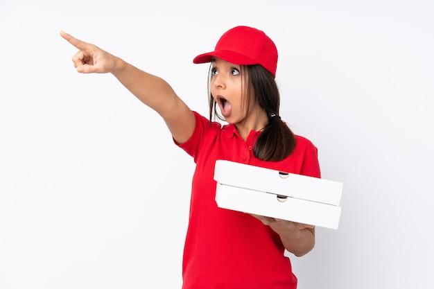 離れて指している分離の白い壁の上の若いピザ配達の女性