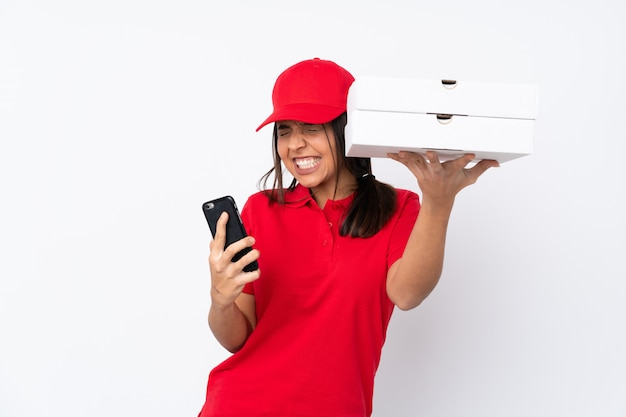 Молодая женщина доставки пиццы по изолированной белой стене с телефоном в положении победы