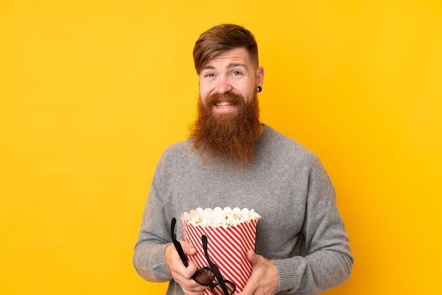 Рыжий мужчина с длинной бородой на изолированной желтой стене держит большое ведро попкорна