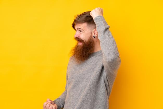 勝利を祝う孤立した黄色の壁の上の長いひげと赤毛の男