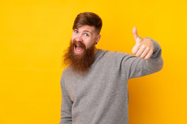 Рыжий мужчина с длинной бородой на изолированной желтой стене с большими пальцами руки вверх, потому что случилось что-то хорошее