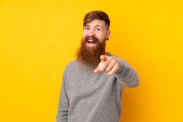 驚いたと正面を指している分離の黄色の壁の上の長いひげを持つ赤毛の男