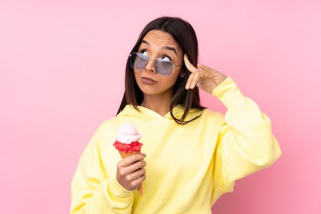 Молодая брюнетка женщина, держащая корнет мороженое над розовой стеной, имея сомнения и мышления