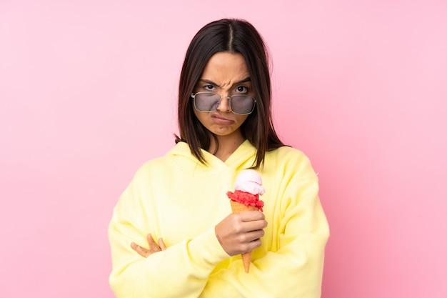 孤立したピンクの壁の気分を混乱させる上にコルネットアイスクリームを保持している若いブルネットの女性