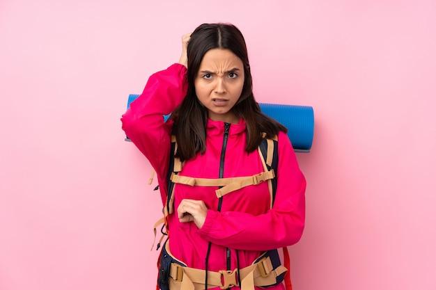 疑問を持つ分離ピンクの壁の上の大きなバックパックを持つ若い登山家女性