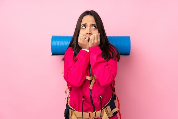 孤立したピンクの壁に大きなバックパックを持つ若い登山家女性