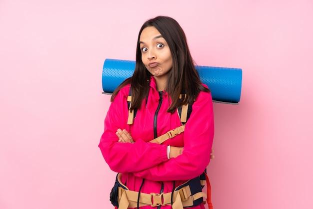 肩を持ち上げながら疑わしいジェスチャーを作る分離のピンクの壁に大きなバックパックを持つ若い登山家女性