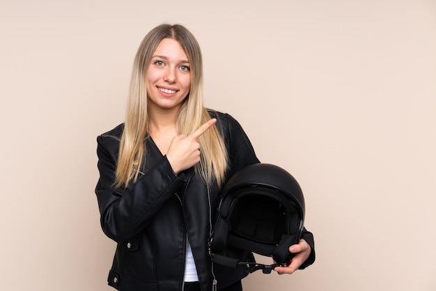 孤立した壁側に指を指す上のオートバイのヘルメットを持つ若いブロンドの女性