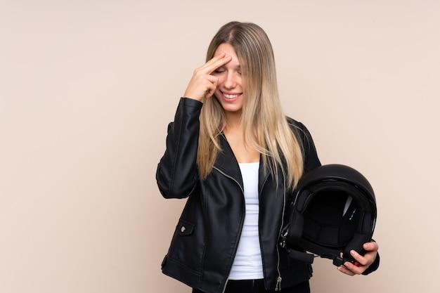 孤立した壁の笑いの上のオートバイのヘルメットを持つ若いブロンドの女性