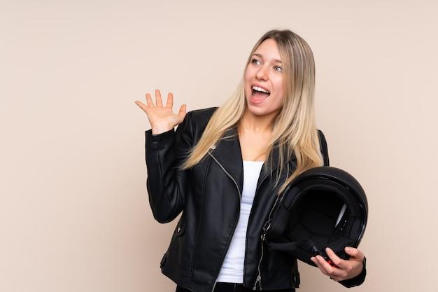 Молодая блондинка с мотоциклетным шлемом над изолированной стеной с удивленным выражением лица