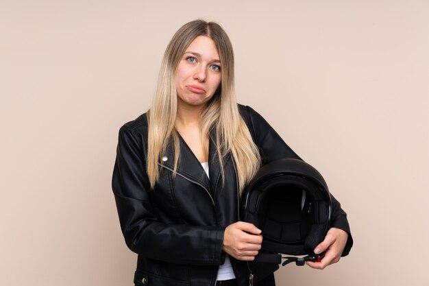 Молодая блондинка с мотоциклетным шлемом на стене