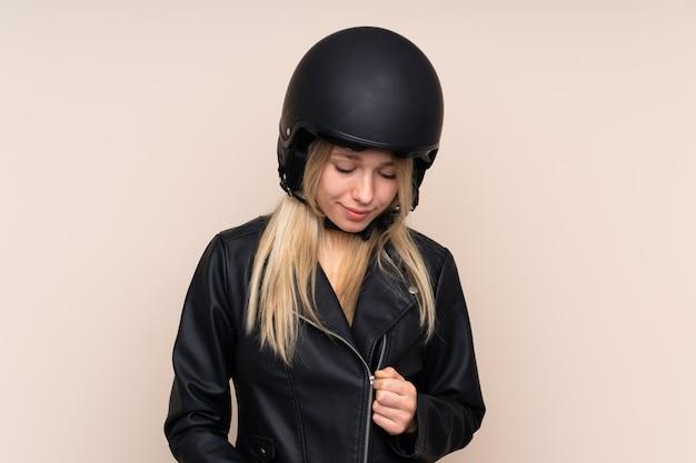 Молодая блондинка с мотоциклетным шлемом над изолированной стеной