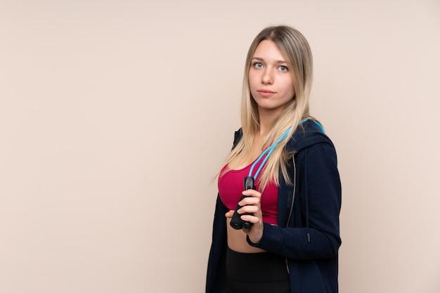 Молодая спортивная блондинка над изолированной стеной со скакалкой