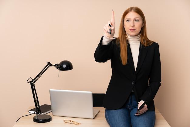 透明なスクリーンに触れるオフィスのビジネスウーマン