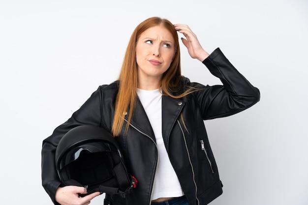 Рыжая молодая женщина с мотоциклетным шлемом сомневается и смущает выражение лица