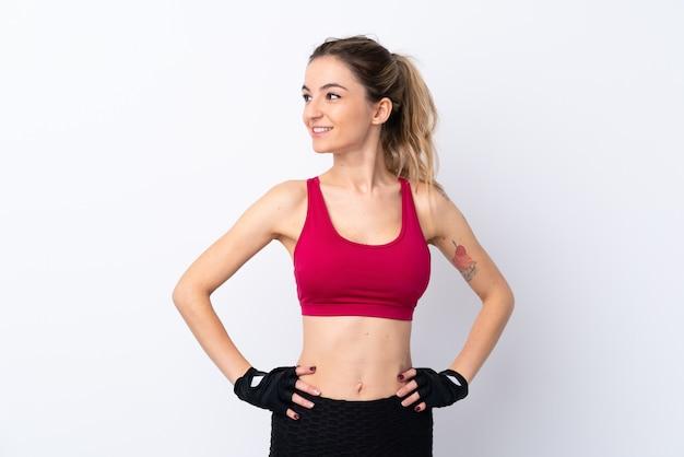 Молодая спортивная женщина позирует с руки на бедра и глядя в сторону