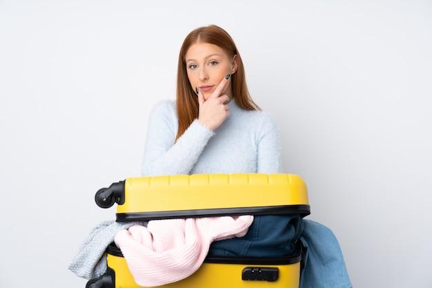 アイデアを考えて服でいっぱいのスーツケースを持つ旅行者女性