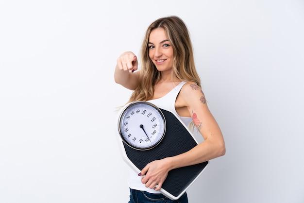 Молодая женщина, держащая весы и указывая на фронт