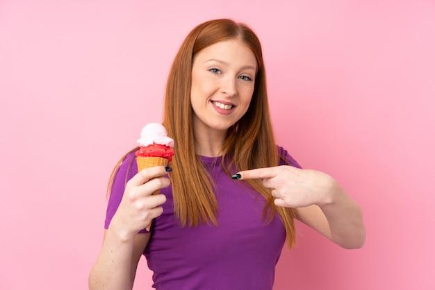 Молодая рыжая женщина с корнет мороженым и указывая его