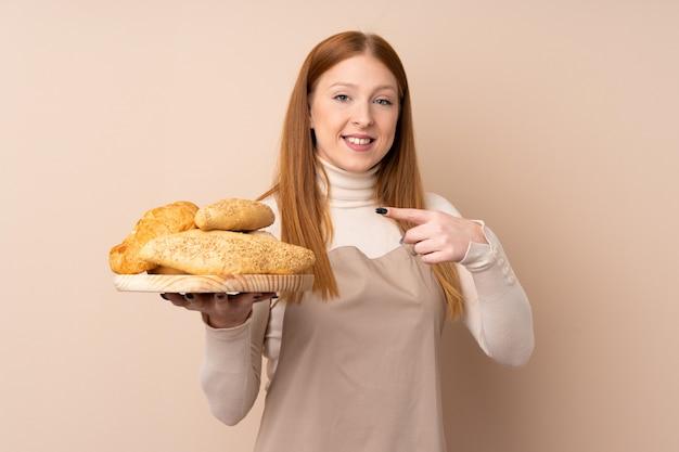 Рыжая молодая женщина в форме шеф-повара. женский пекарь держит стол с несколькими хлебов и указывая его