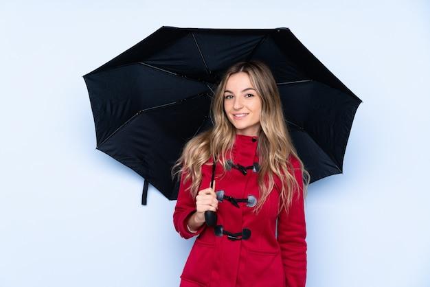冬のコートと多くの笑みを浮かべて傘を保持している若い女性