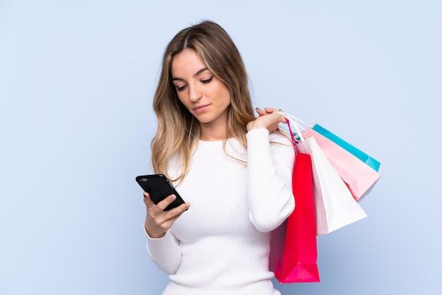Молодая женщина, держащая сумок и написав сообщение со своего мобильного телефона другу