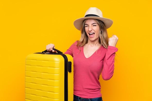 旅行スーツケースと帽子と休暇で若い女性