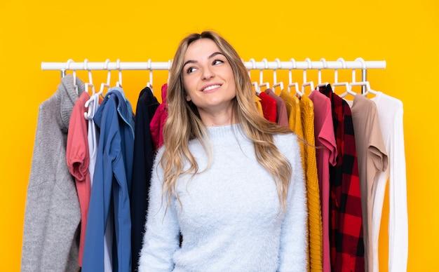 Молодая женщина в магазине одежды, смеясь и глядя вверх