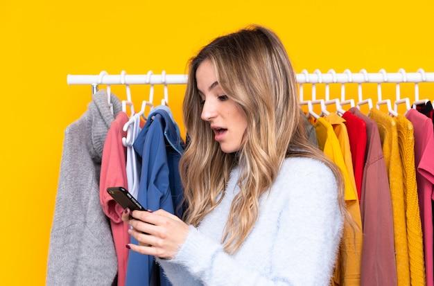 Молодая женщина в магазине одежды с мобильным