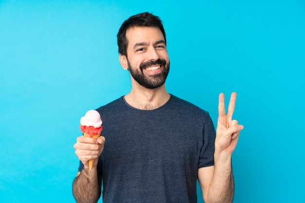 両手で勝利のサインを示すコルネットアイスクリームと若い男