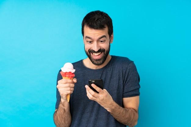 Молодой человек с мороженым корнет удивлен и отправив сообщение