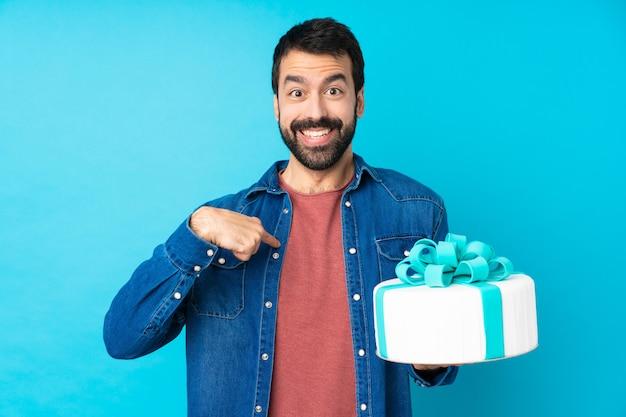 Молодой красивый мужчина с большой торт с удивленным выражением лица