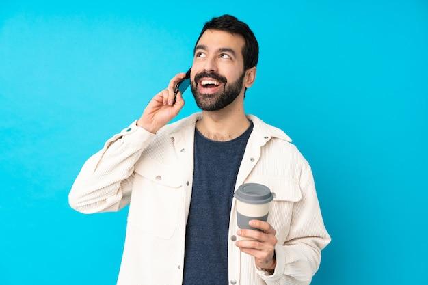 Молодой красавец с белой вельветовой курткой держит кофе на вынос и мобильный