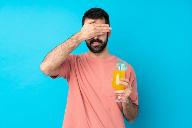 Молодой человек за коктейль, охватывающий глаза руками