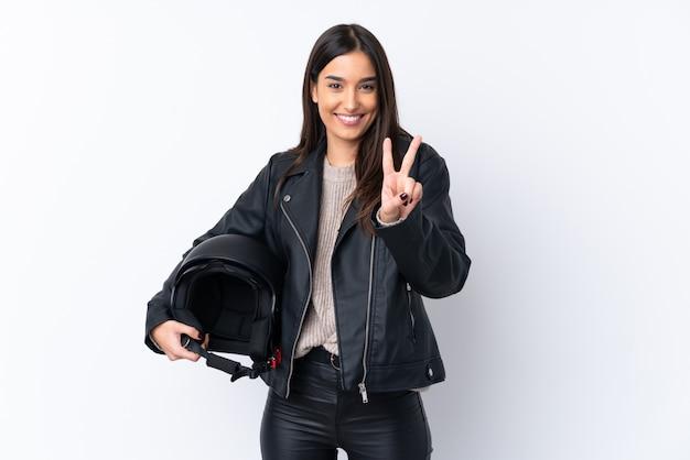 Молодая брюнетка женщина с мотоциклетный шлем, улыбаясь и показывая знак победы