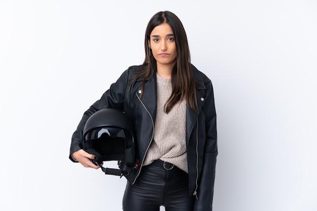 悲しそうな表情でオートバイのヘルメットを持つ若いブルネットの女性