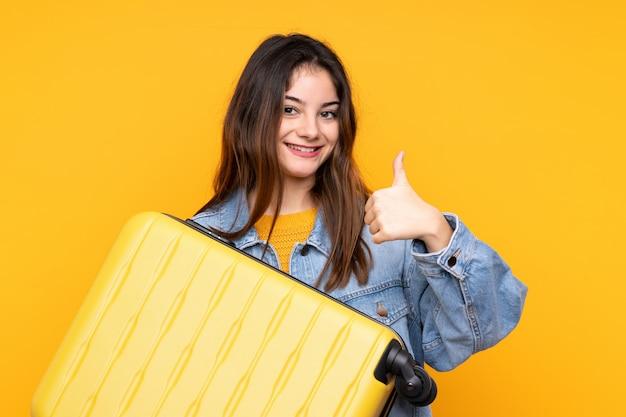旅行スーツケースと親指アップと休暇で黄色の壁に若い白人女性