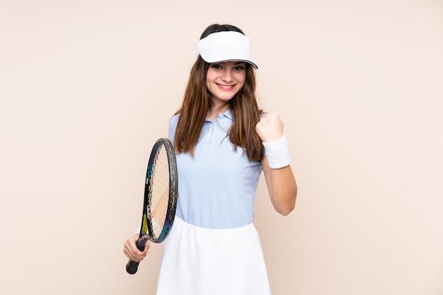 Молодая кавказская женщина на бежевой стене играет в теннис и празднует победу