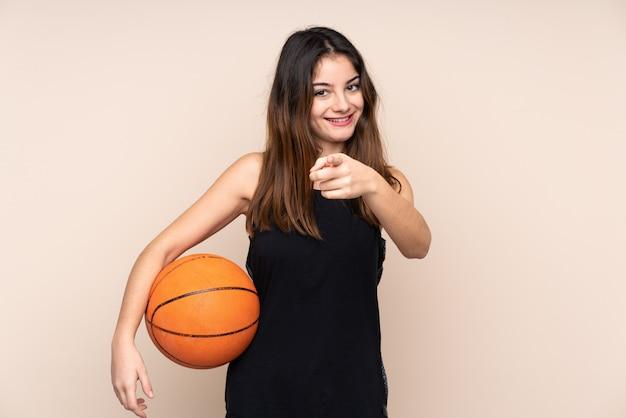 Молодая кавказская женщина на бежевой стене играет в баскетбол и указывая на фронт