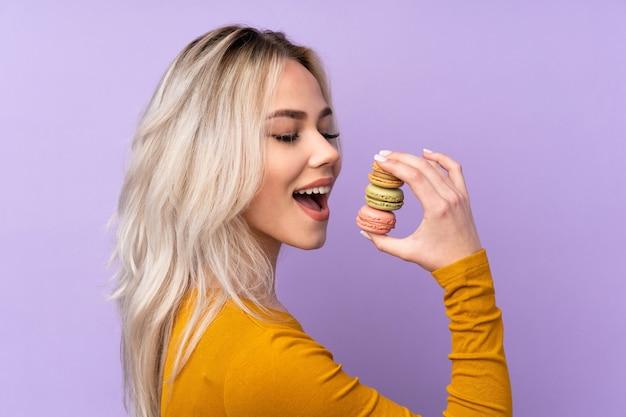 カラフルなフランスのマカロンを押しながらそれを食べる紫色の壁の上のティーンエイジャーの女の子