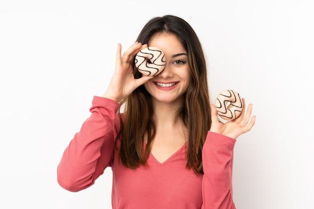 Молодая кавказская женщина на розовой стене держа пончик и счастливый